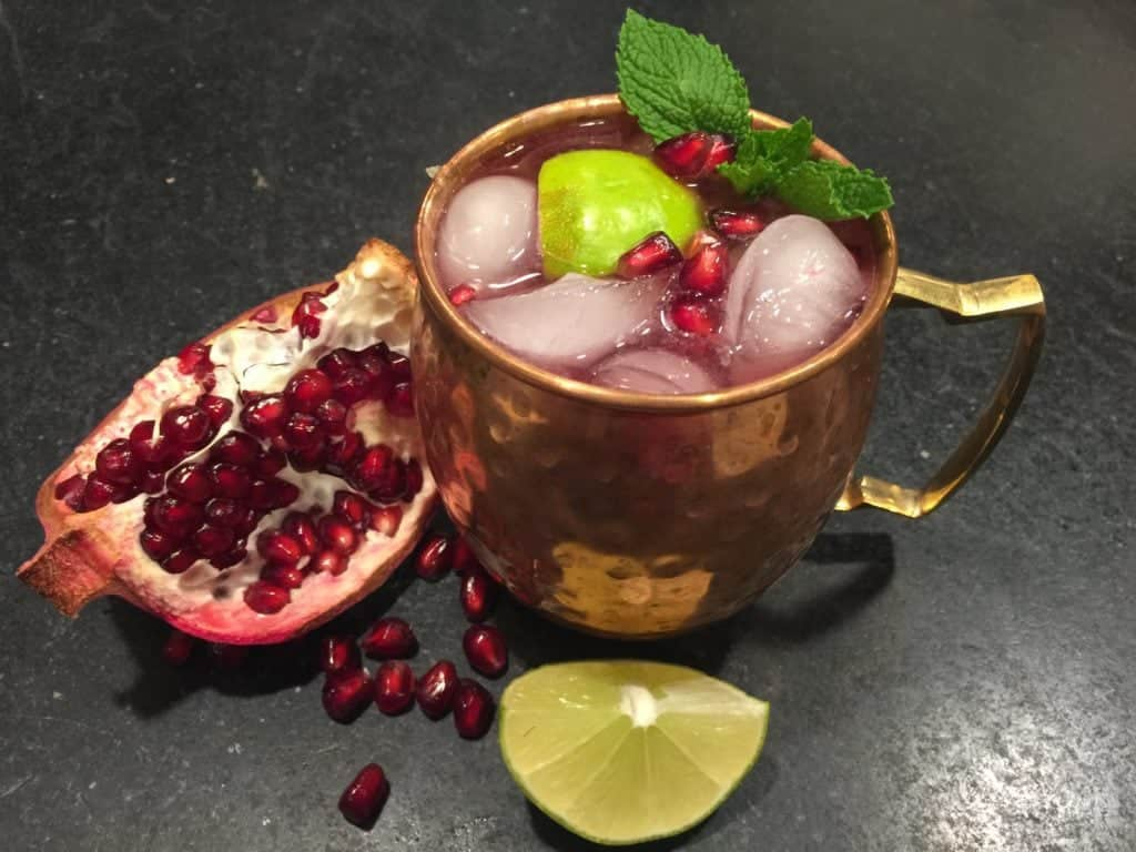 Copper mug filled with ice and pomegranate mule with sprig of mint, wedge of lime and pomegranate arils.