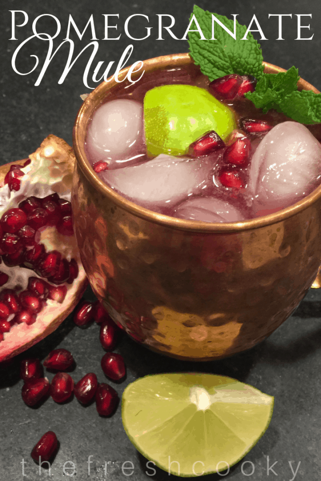 Pomegranate Mule in copper mug with ice and pomegranate arils on top with a fresh twist of lime and mint.