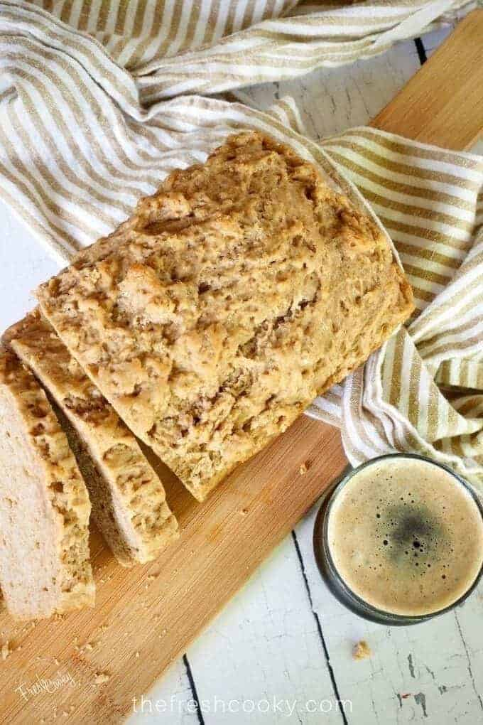 top down shot of a loaf of beer bread with two slices. A striped tea towel lies underneath and over a cutting board with a glass of dark beer in the foreground.