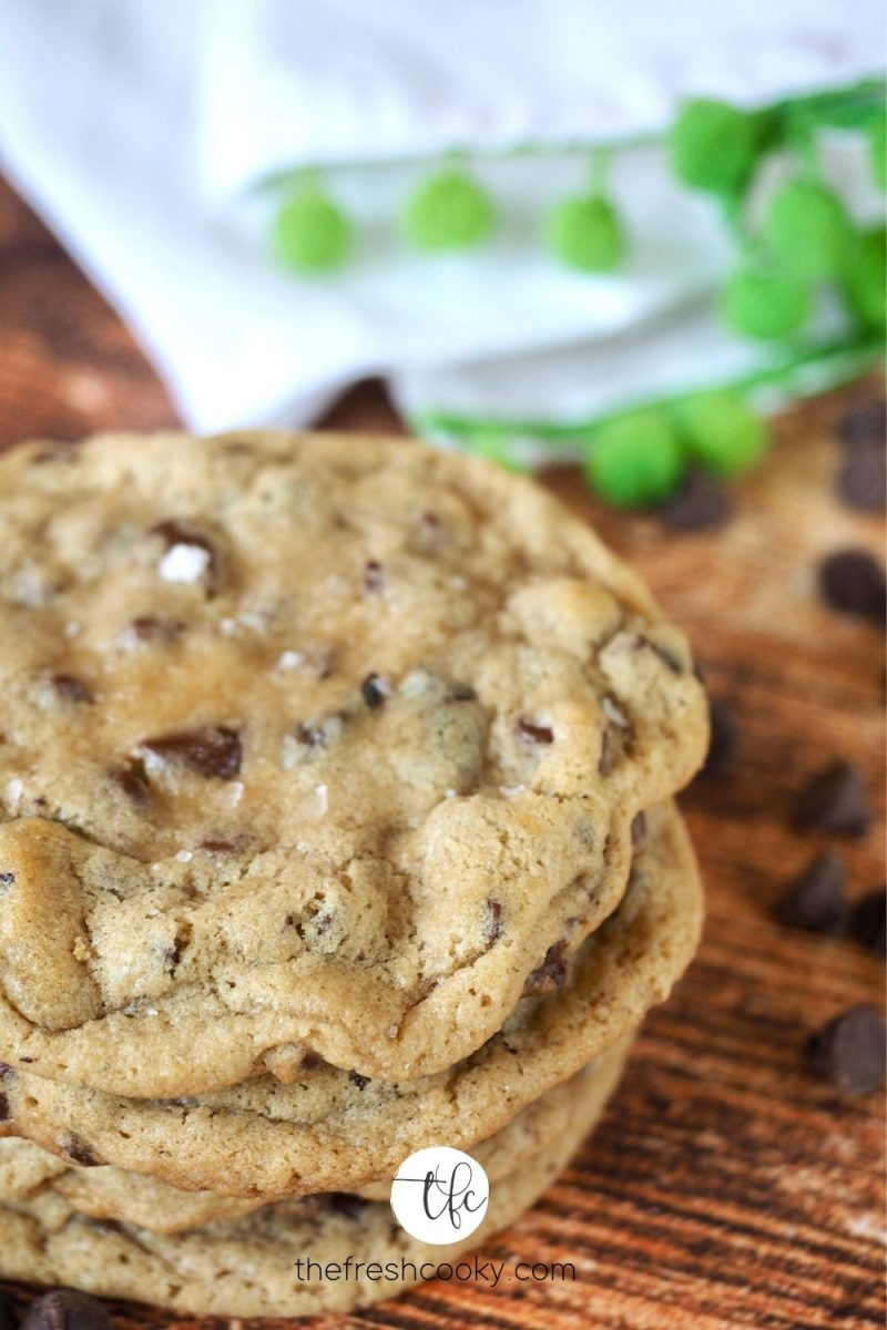 Stack of 4 chocolate chip cookies on wooden table with chocolate chips sprinkled about.