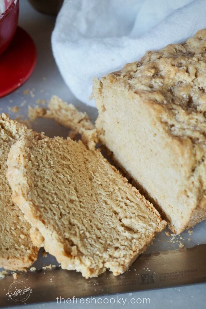 Close up of beer bread with two pieces sliced on a cutting board with serrated knife.