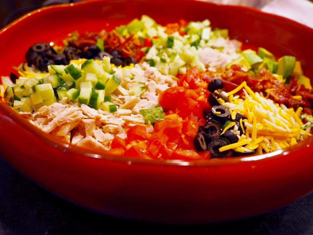Side view of large cobb salad in shallow red bowl.