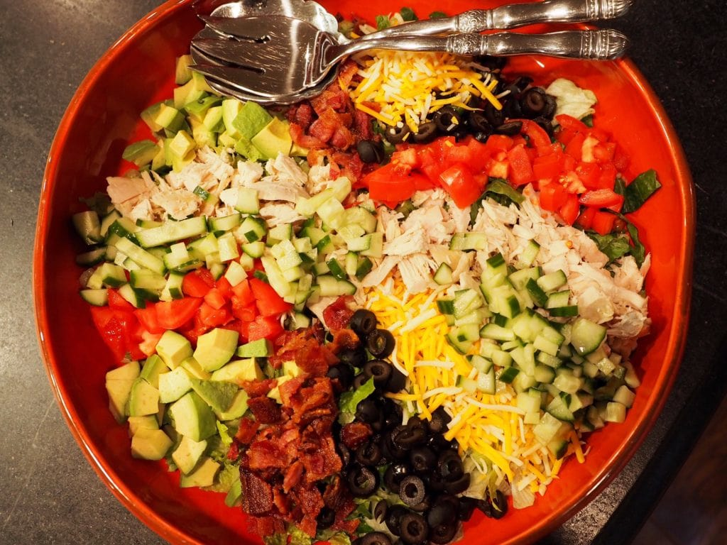 Top down image of large chicken cobb salad with serving spoons.