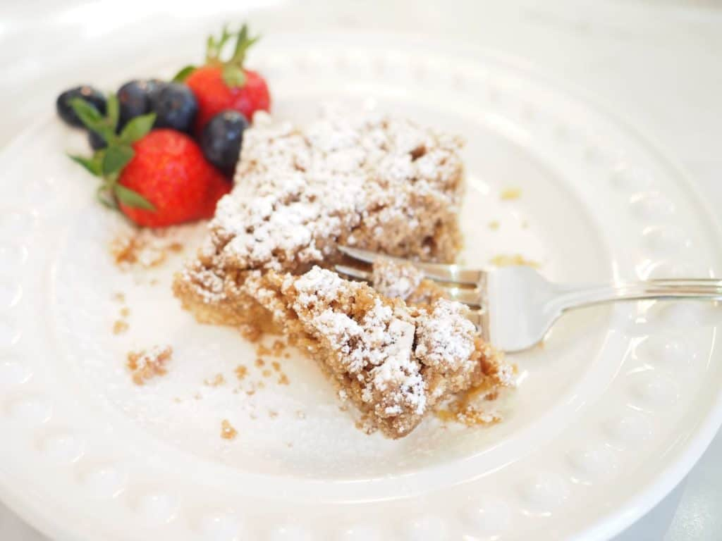 Square of Starbucks Coffee Crumb Cake on white plate with fork pie and a few berries.