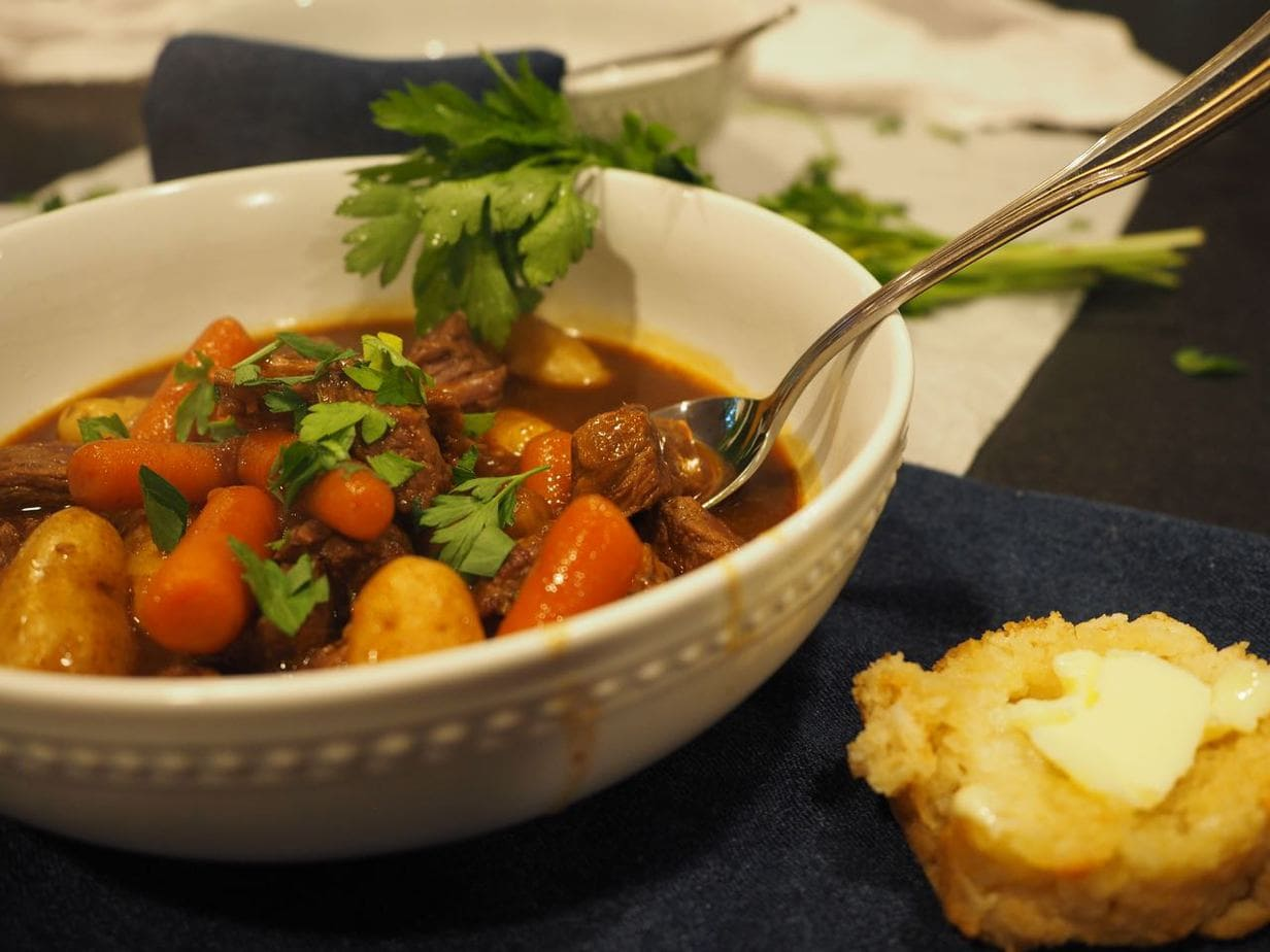 Dutch Oven Beef Stew in bowls with beer bread nearby.