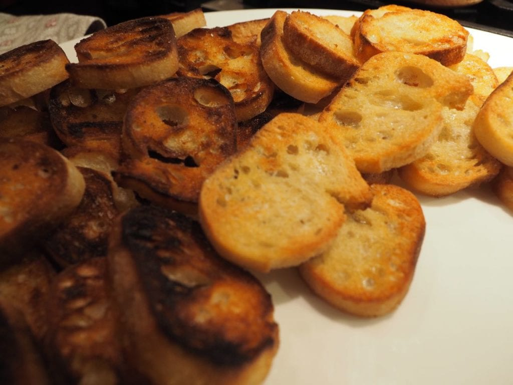 Plate full of toasted crostini slices (sliced french baguette)
