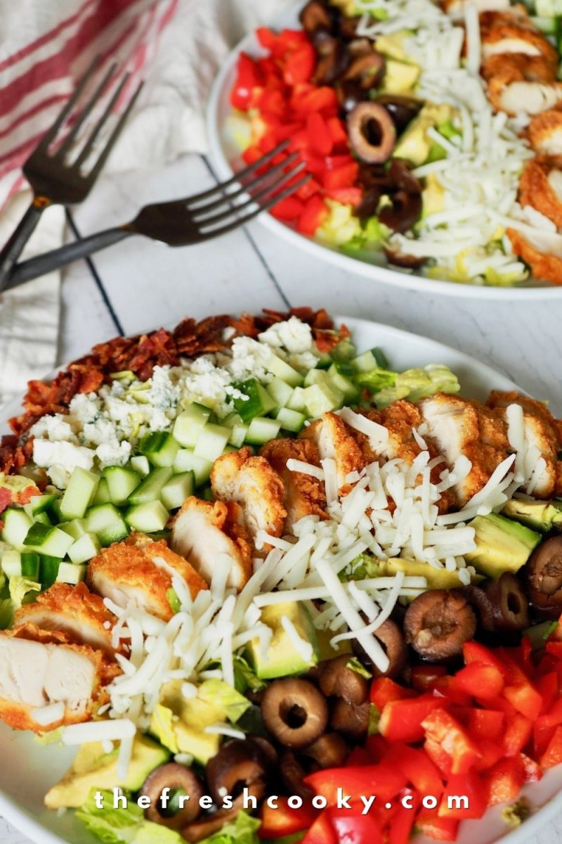 Plates of chicken cobb salads with forks and dressing.