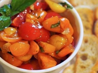 Easy and AMAZING Tomato Bruschetta is the perfect appetizer for any occasion. Warm garlic olive oil poured over fresh cut grape tomatoes, fresh basil and drizzled with balsamic vinegar. Spread a little creamy goat cheese on the crostini then top with bruschetta. #thefreshcooky #bruschetta #tomatoes #appetizer #easy