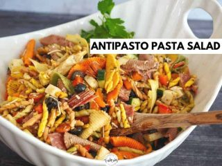 large white bowl of pasta salad with wooden spoon