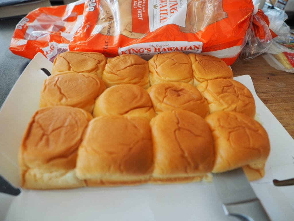 A tray of King's Hawaiian rolls on cutting board with knife slicing through.