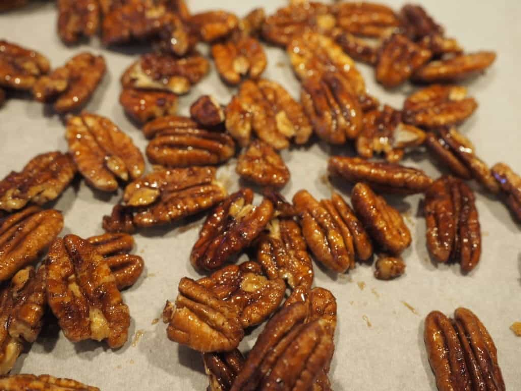 A tray of sticky candied pecans on parchment paper.