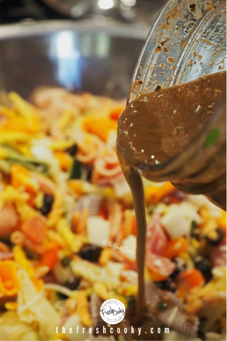balsamic vinaigrette pouring from mason jar onto pasta salad