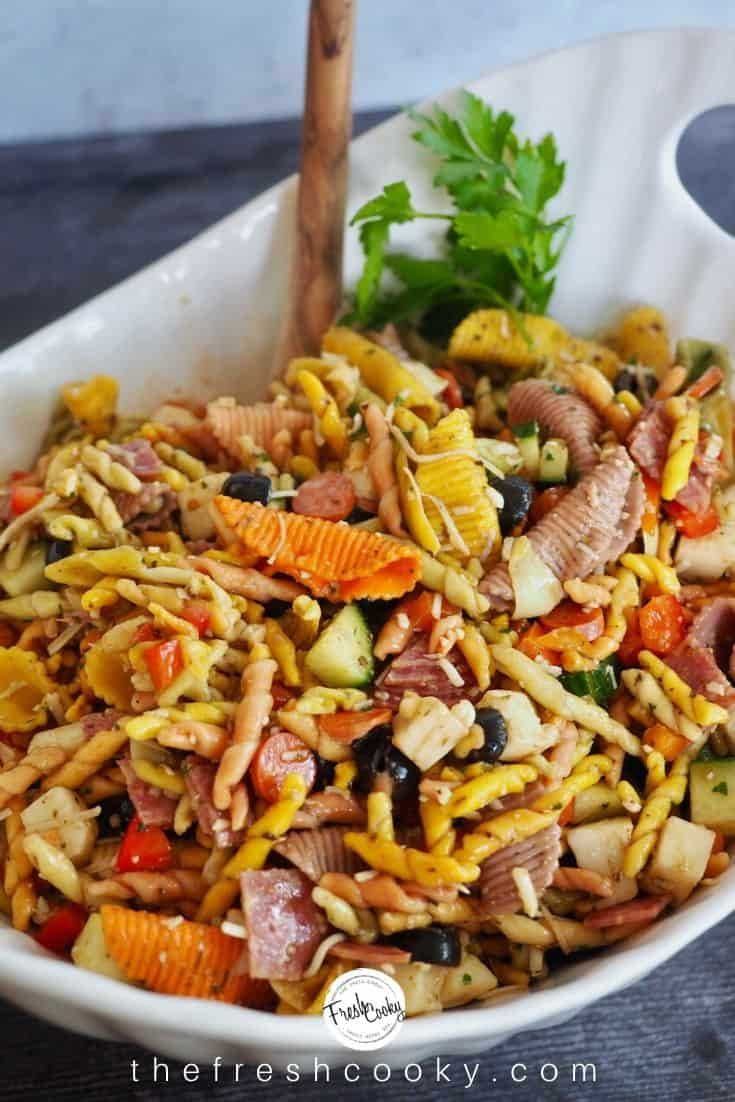 pasta salad in large white bowl with wooden spoon