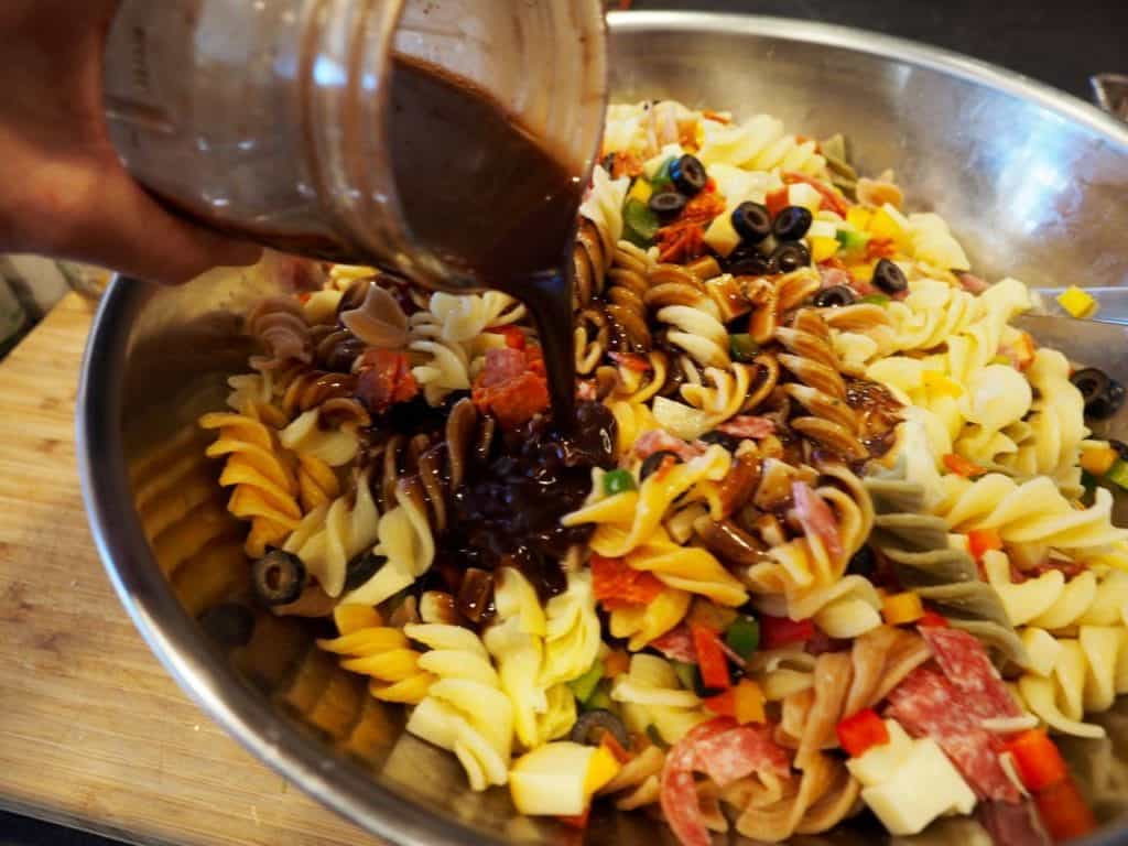 Italian Pasta Salad pouring balsamic dressing | wwwthefreshcooky.com