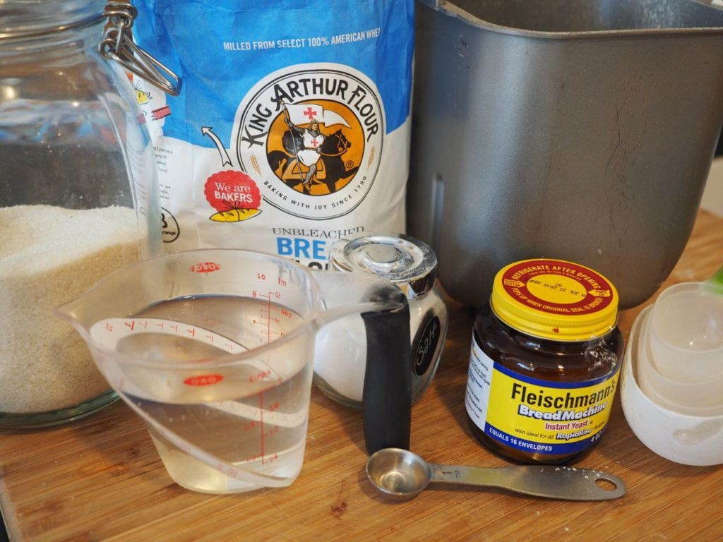 Ingredients for easy yeast rolls, left to right. Sugar, bread flour, bread machine, yeast, salt and water (plus egg, not shown)