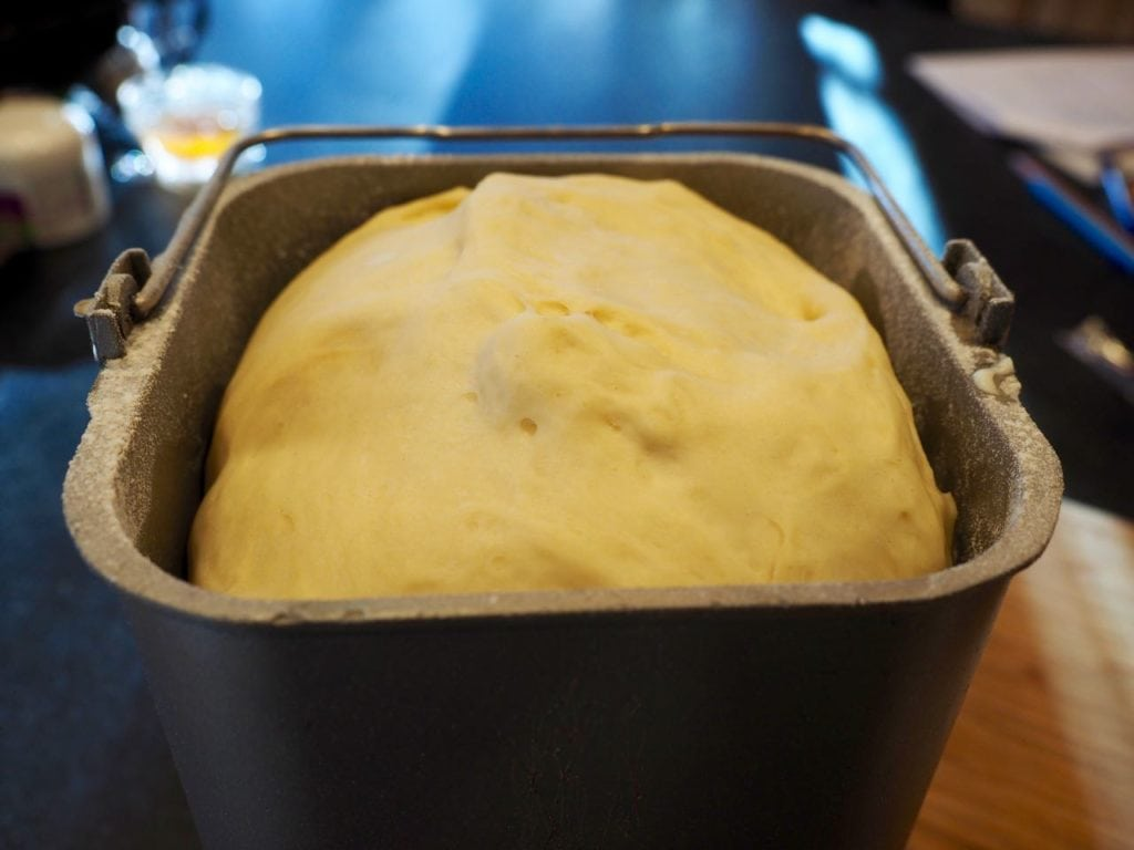 Risen dough to the top of the bread machine bread pan.