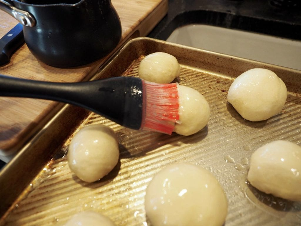 Brushing tops of rolls with melted butter