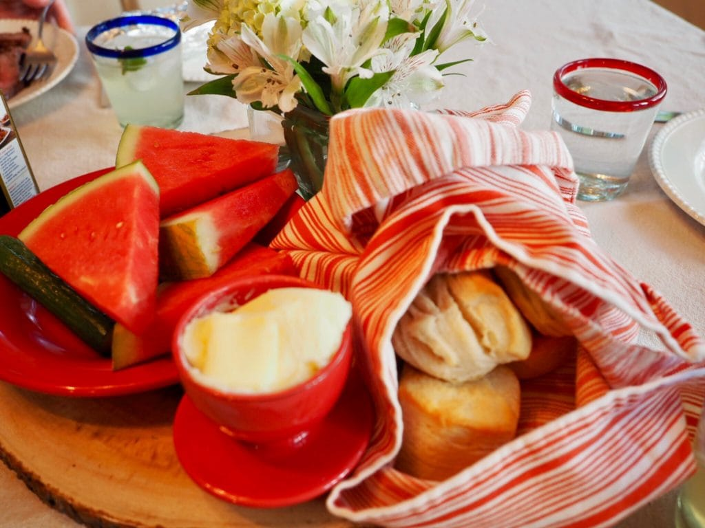 Summer table set with flowers, wedges of fresh watermelon, hot biscuits and butter in a crock. | www.thefreshcooky.com