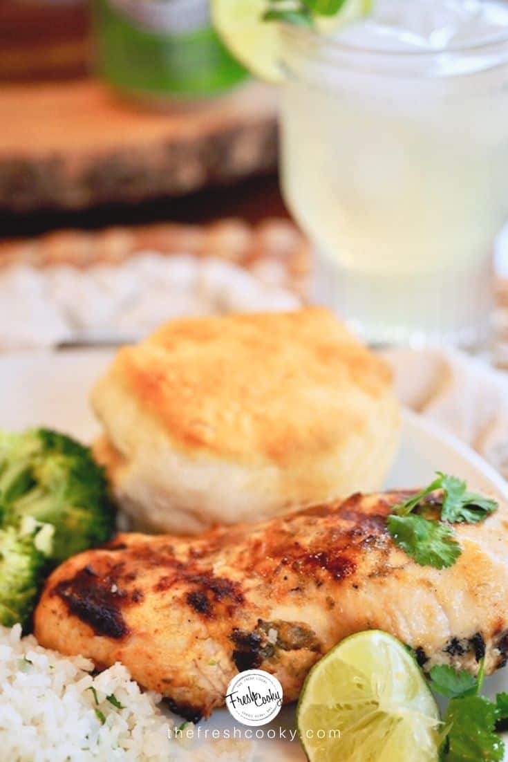 Best coconut lime chicken marinade with chicken breast, fresh lime, biscuit amd lemonade in background.