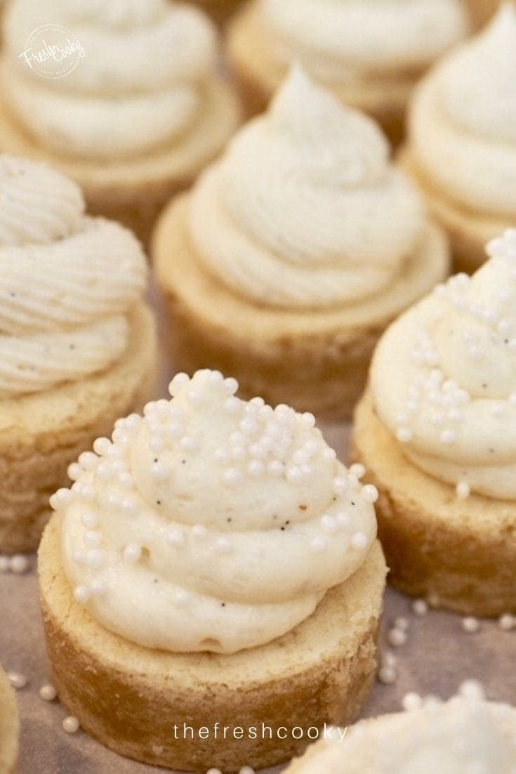 Close up, sugar cookie bite frosted with a swirl of vanilla frosting and decorated with pearl candies.