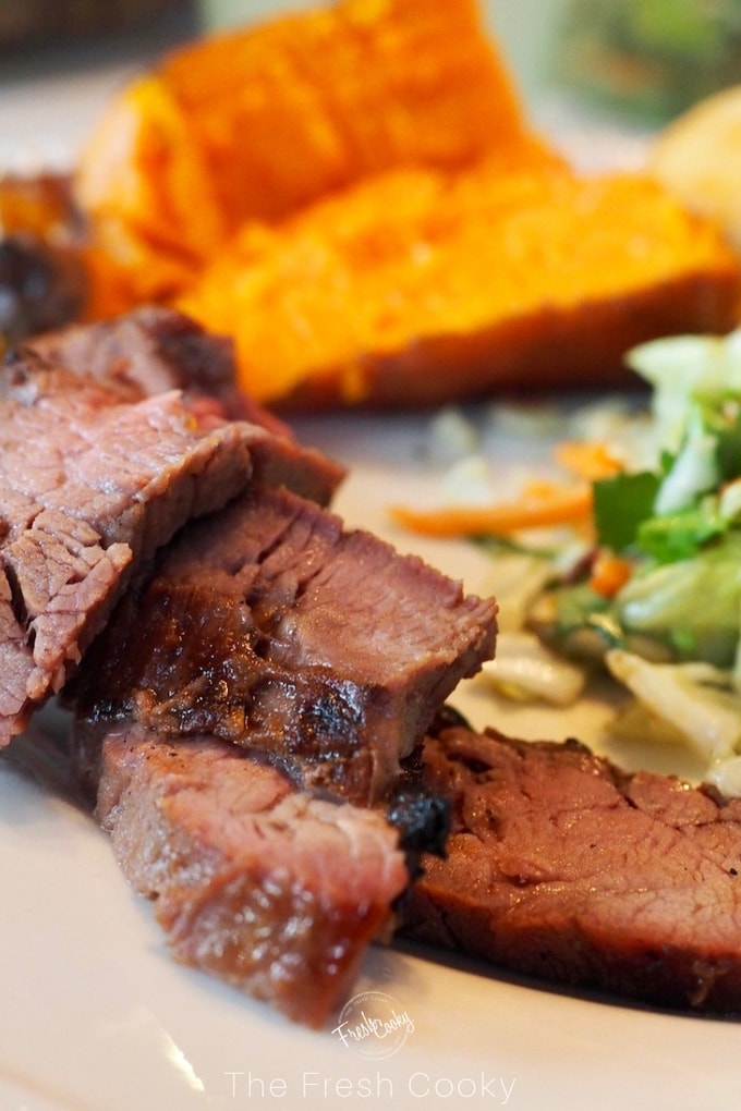 slices of flank steak up close with sweet potato in background and salad on plate.