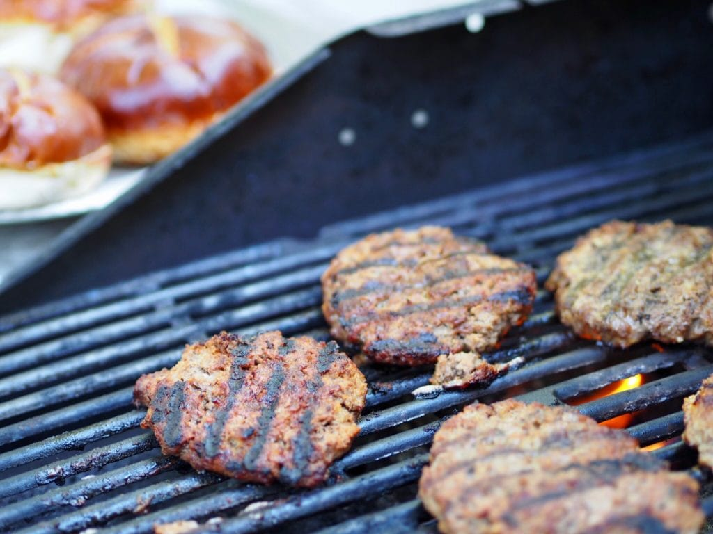 juicy burgers on the grill with grill marks and pretzel buns in the background. thefreshcooky.com