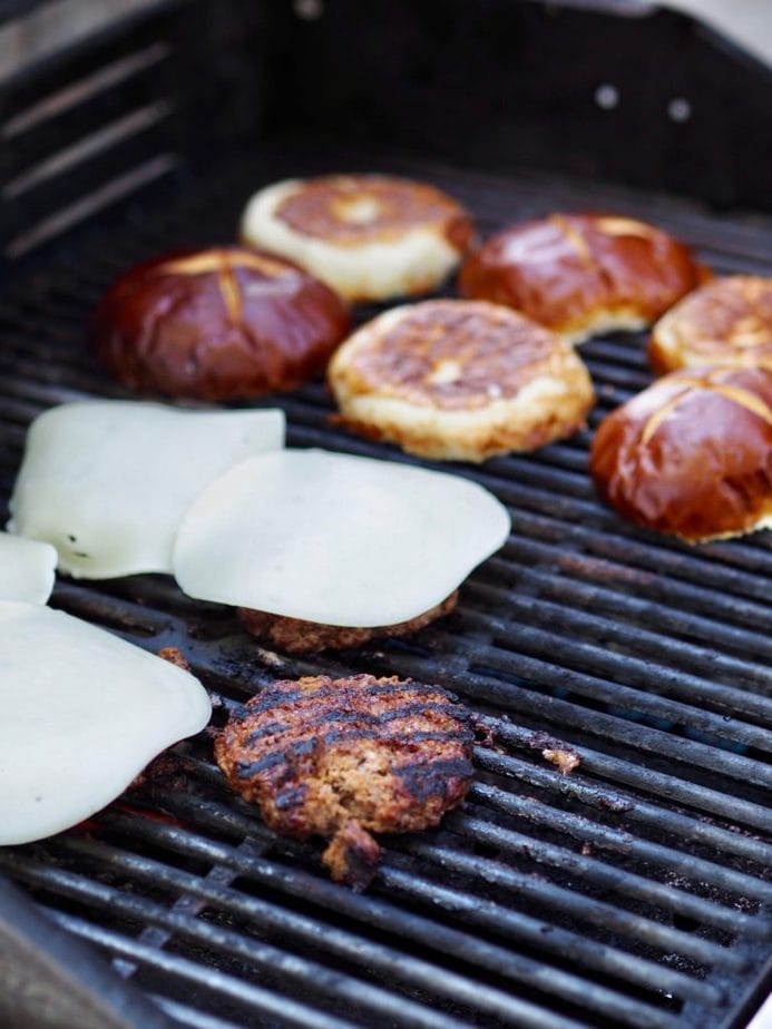 provolone cheese topped hamburgers on grill with one burger left without cheese, pretzel buns warming on side of grill. thefreshcooky.com