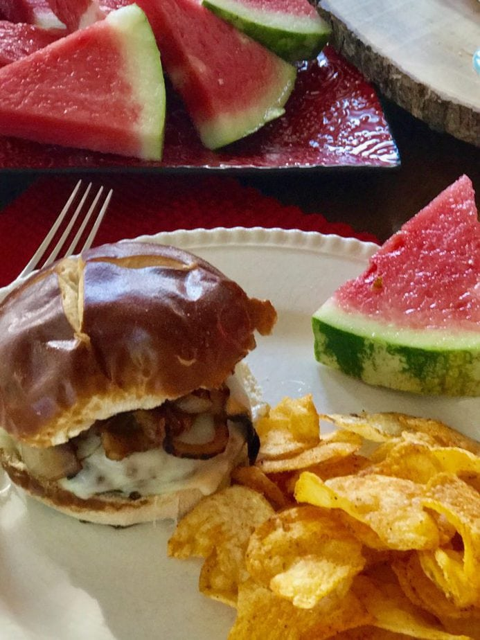 A plate with a juicy grilled cheeseburger, topped with caramelized onions on a pretzel rolls with barbecue potato chips and a wedge of fresh, juicy watermelon. thefreshcooky.com