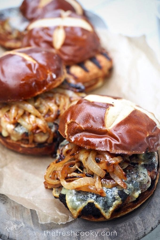 Close up of a grilled cheeseburger with crisp edges cheese, tender, stringy caramelized onions topped with a salty pretzel bun. thefreshcooky.com