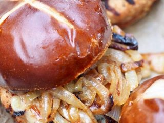 Closeup of turkey burger, grilled with caramelized onions topped with a pretzel roll. thefreshcooky.com