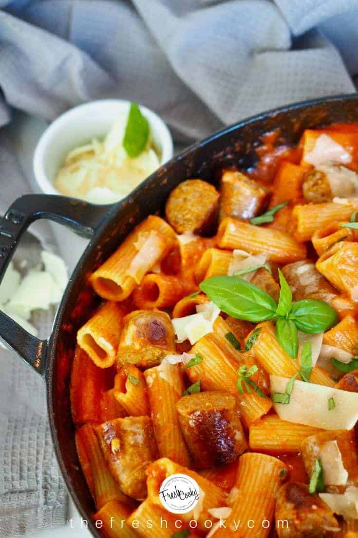 Large pan filled with creamy penne alla vodka pasta with Italian sausage, shaved Parmesan and fresh basil.