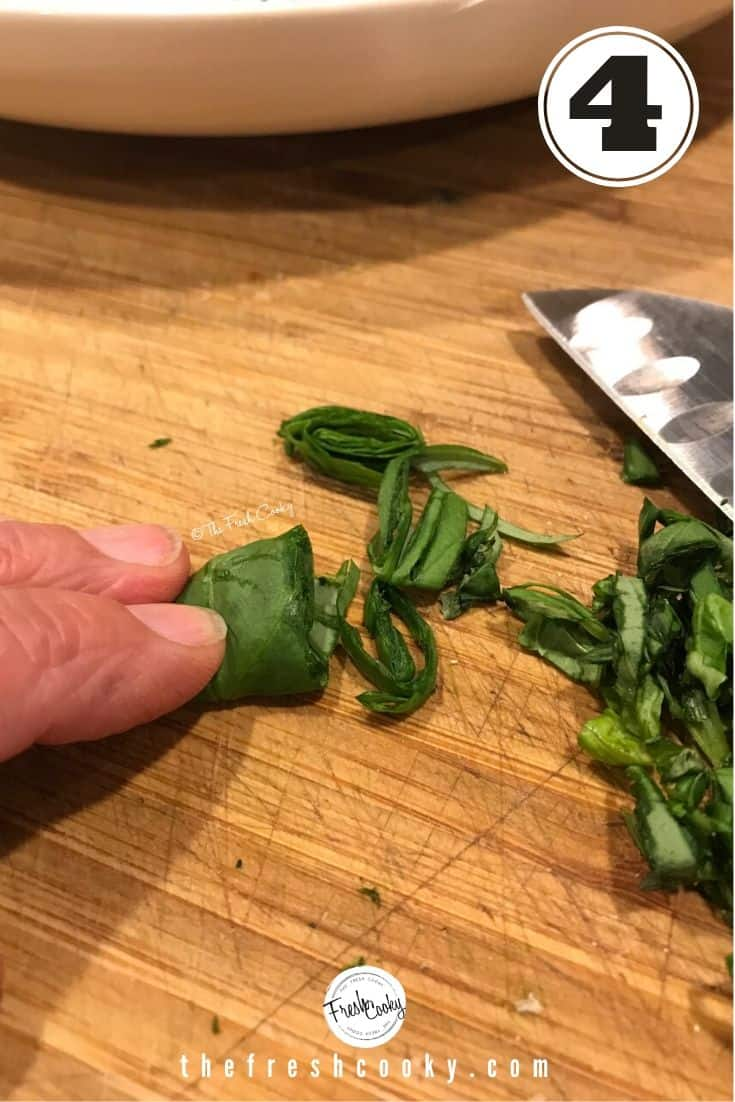 slicing or chiffonade of fresh basil with fingers holding rolled basil leaves, slices and a knife off to the side.