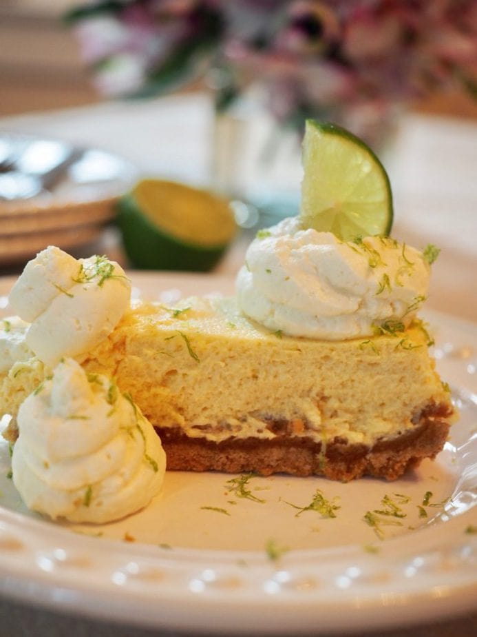 Slice of key lime torte on a white plate with 3 dollops of whipped cream and a slice of lime, with lime and plates and a vase of flowers in the background.