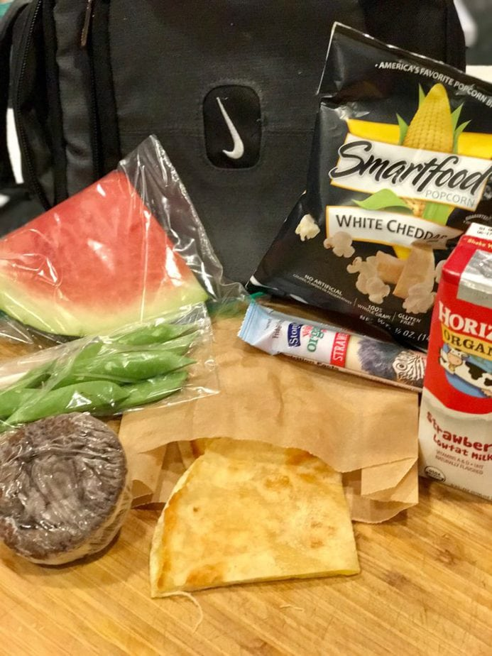 Left to right, wedge of watermelon, white cheddar smartfood,sugar snap peas in baggie, cheese quesadilla in wax paper, Stonyfield Farms organic yogurt tube, Strawberry milk,