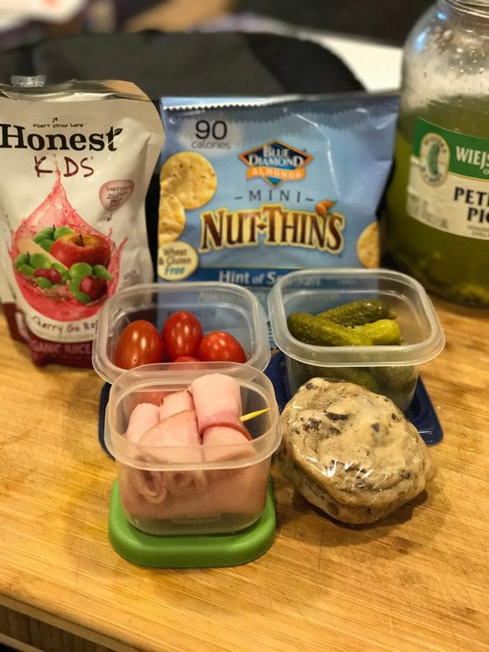 school lunch. Honest Kids cherry fruit punch pouch, mini nut things, petite dill pickles in jar, and some in small plastic container, grape tomatoes and rolled ham with toothpick in small rubbermaid. Two chocolate chip cookies, frozen and in plastic wrap.
