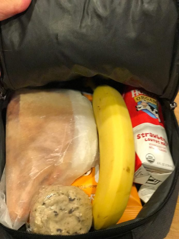 Lunch Box filled with slice of pizza in wax paper bag, banana, strawberry milk, cookies