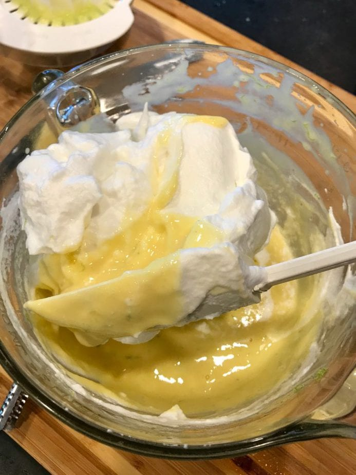 Key lime mixture in glass mixing bowl with large spatula folding or turning whipped egg whites into the batter.