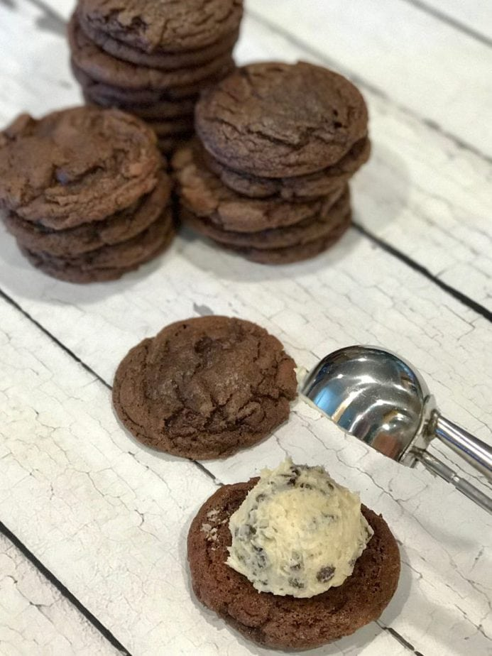 Soft, chewy brownie cookies sandwiching the most amazing Chocolate Chip Cookie Dough Frosting #sandwichcookies #brownie #cookies #cookiedoughfrosting #lunchboxtreats #browniesandwichcookies #thefreshcooky #holidaycookierecipes #christmascookieexchange #holidaybakingrecipes