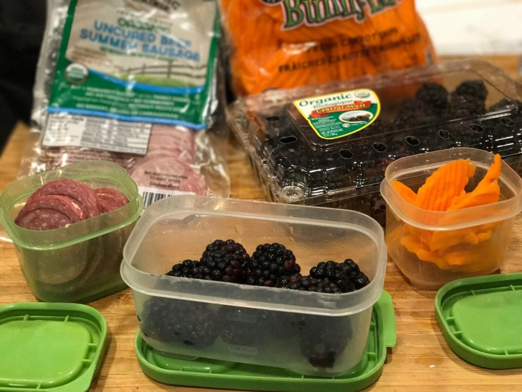 image on cutting board with small tupperware containers filled left to right with summer sausage, organic blackberries, carrot chips