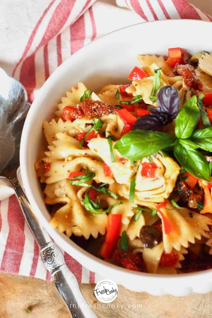 white bowl filled with colorful Italian Pasta salad with bowtie pasta.