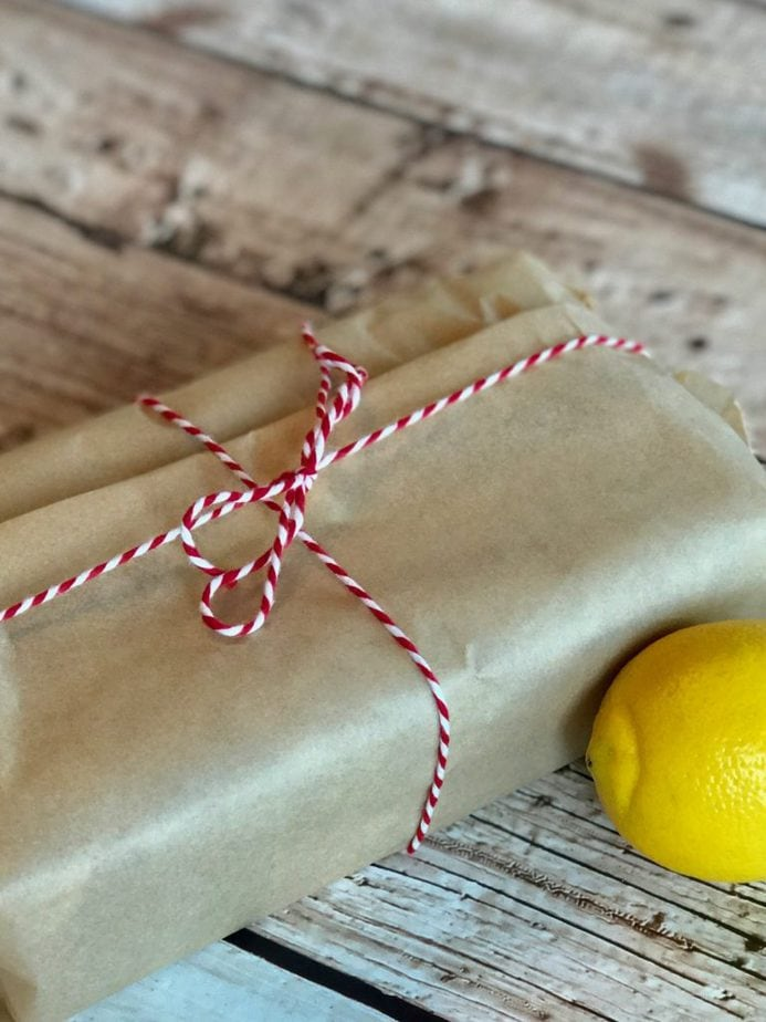 A loaf of lemon zucchini bread wrapped in natural parchment paper tied with red and white bakers twine.