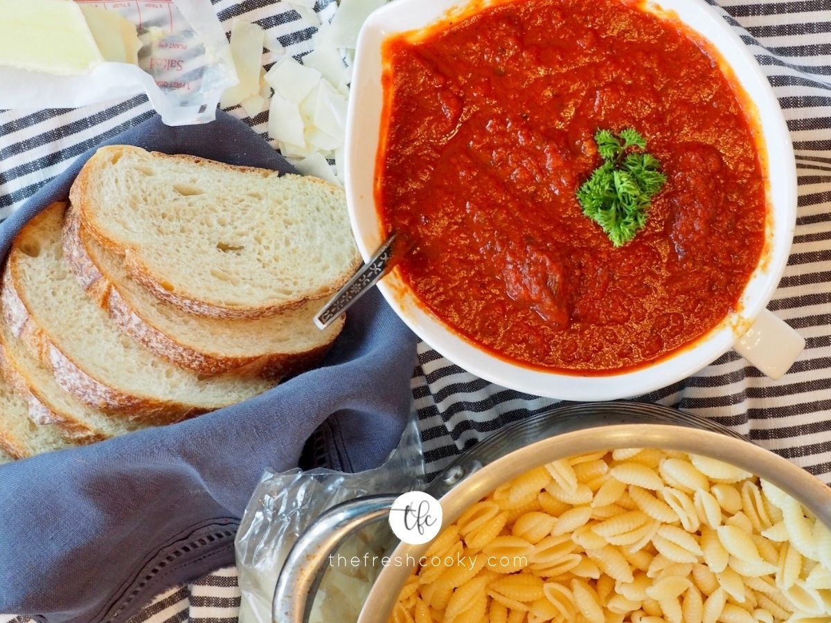 Bowl of spaghetti sauce with cooked pasts and bread nearby.