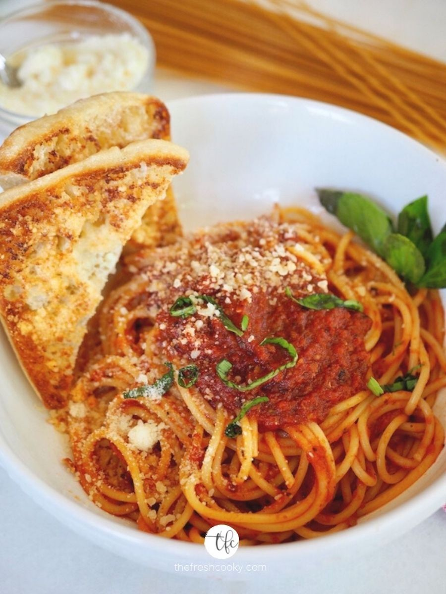 White bowl filled with spaghetti with red sauce on top, slices of garlic toast on the side with fresh basil on top.