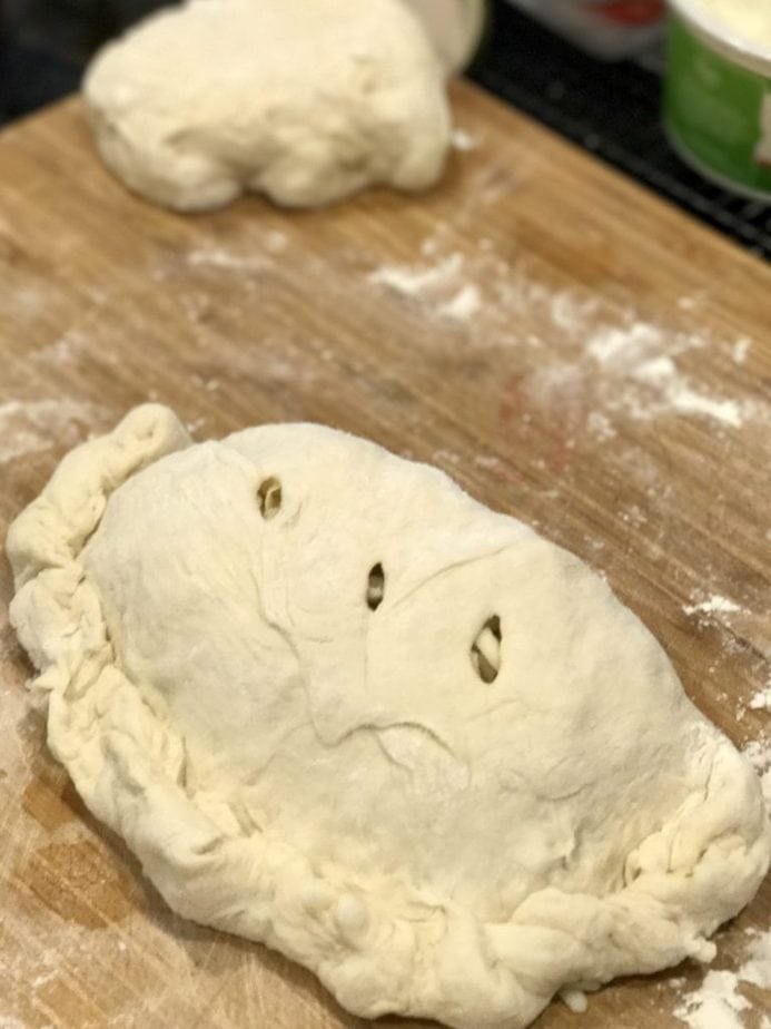 Easy Calzone on a cutting board ready for the oven, pinched edges and 3 slits cut into the top of the pizza pie.