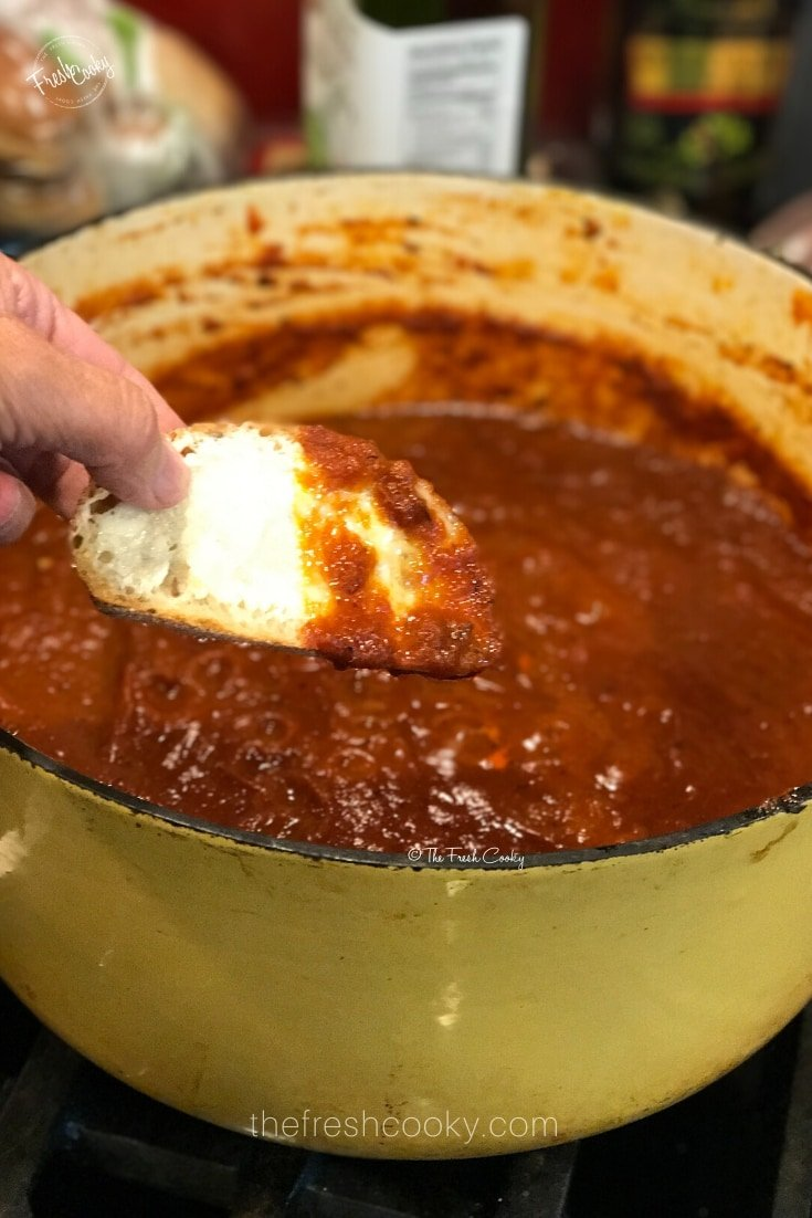 Large gold dutch oven filled with rich, dark red best spaghetti sauce with hand dipping in small piece of bread into sauce.
