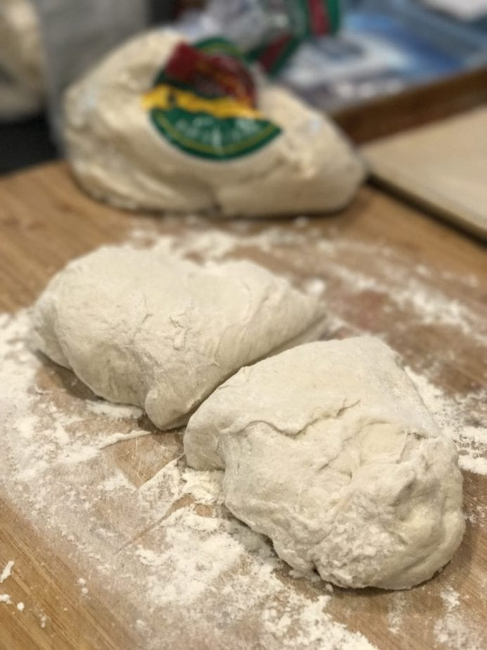 Image of pizza dough, on cutting board with flour and cut in half ready to roll for easy calzones