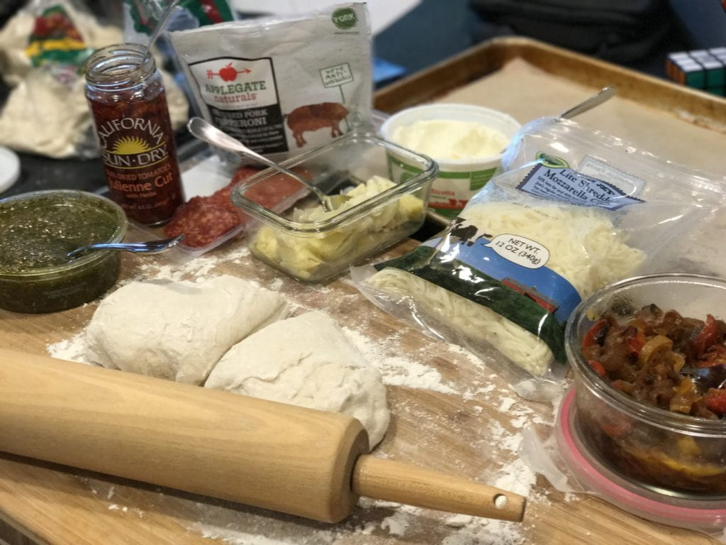 Easy Calzones ingredients shot. Left to Right. Pesto, Sun Dried Tomatoes, natural pepperoni, artichoke hearts, ricotta cheese, mozzarella cheese, caramelized peppers and onions, pizza dough and rolling pin.