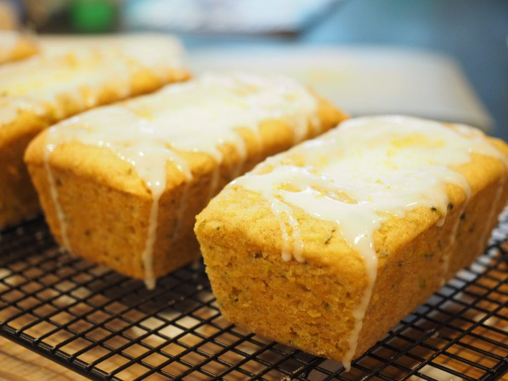 Mini Loaves of Lemon Zucchini Quickbread sitting on a cooling rack with drizzle of glaze over the tops | www.thefreshcooky.com