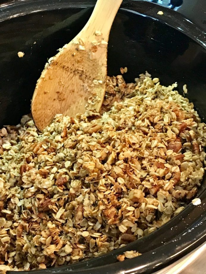 Stirring the granola every 15 minutes, wooden spoon in crockpot.