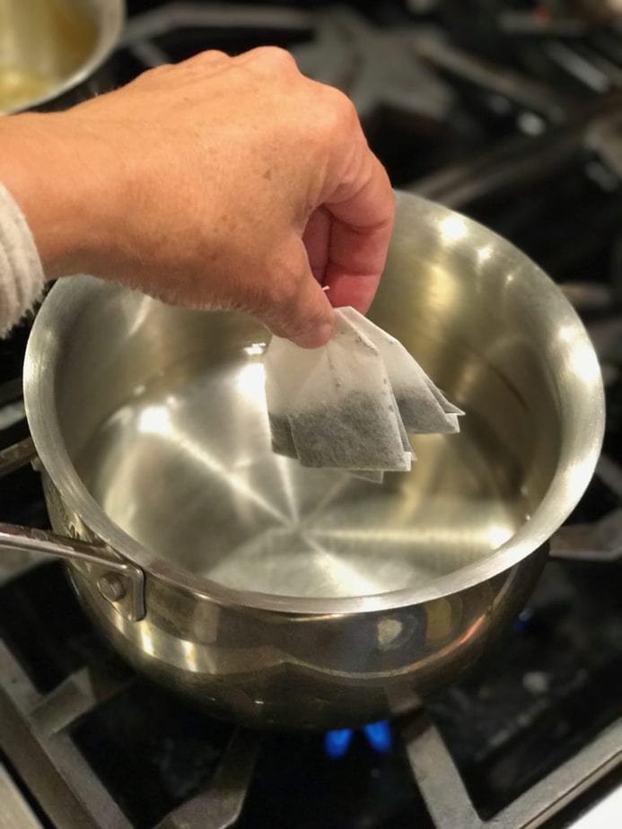 Hand adding tea bags to simmering water on stove for Chai Tea Latte